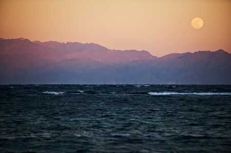Full moon rising over sea and mountains Stock Photo