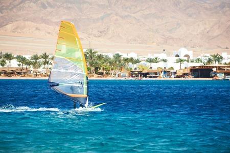 Windsurfing sail on the blue sea against coast