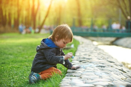 Little boy drawing with sidewalk chalk in the park.