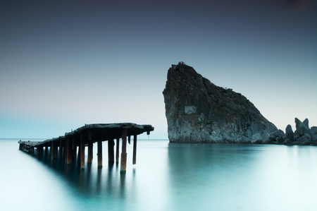Old decaying and dilapidated pier with smooth sea and rock