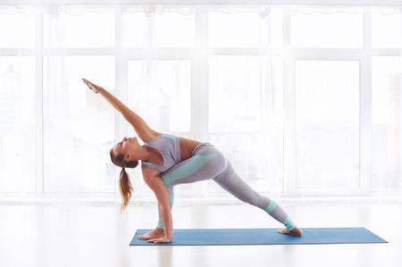 Beautiful young woman practices yoga asana Parivritta Parshvakonasana - Revolving side angle posture at the yoga studio Stock Photo
