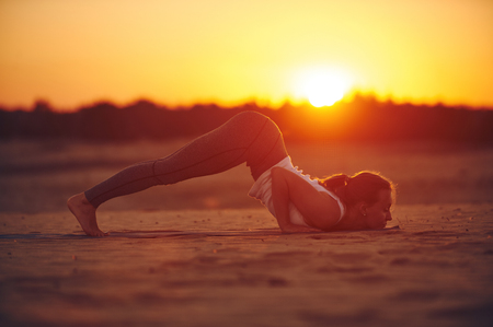 Young woman is doing yoga asana Ashtanga Namaskarasana - eight limbed salutation pose in the desert at sunset. Imagens