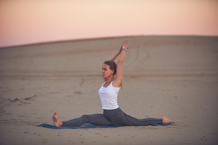 Beautiful young woman practices yoga asana Hanumasana - monkey king pose in the desert at sunset.