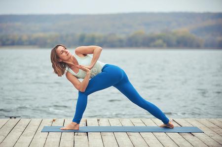 Beautiful young woman practices yoga asana Parivritta Parshvakonasana - Revolving side angle Pose on the wooden deck near the lake Reklamní fotografie
