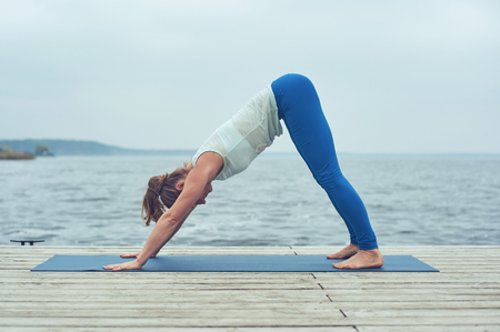 Beautiful young woman practices yoga asana downward facing dog on the wooden deck near the lake Stock Photo