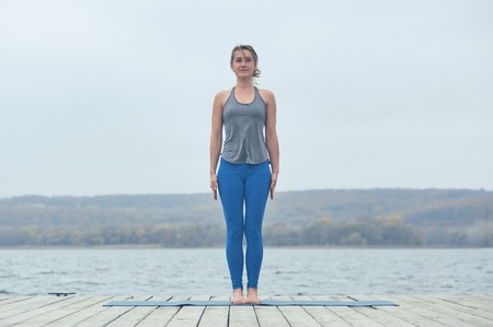 Beautiful young woman practices yoga asana Tadasana - Mountain pose on the wooden deck near the lake Stock Photo