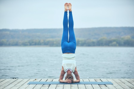 Beautiful young woman practices yoga asana Shirshasana - Headstand pose on the wooden deck near the lake