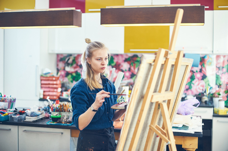 Young Woman Artist Working On Painting In Studio. Selective focus on foreground. Imagens