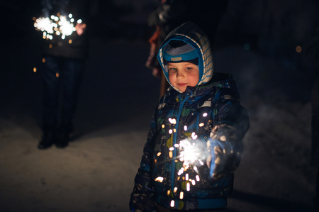 boy holds a sparkler in his hands while celebrating a new year on the street at night. Фото со стока