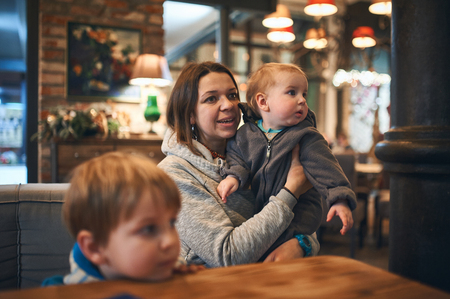 mother with two kids in cafe waiting for order