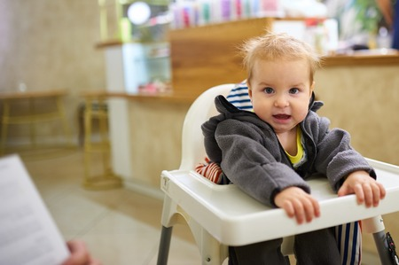 Little baby boy sitting in high chair in cafe Фото со стока