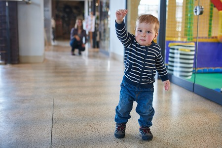 Toddler walking in the shopping center with his mom on background.