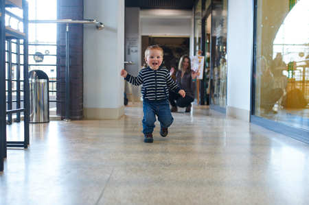 Toddler running in the shopping center with his mom on background.