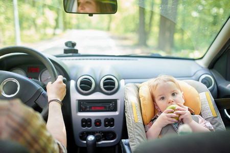 Young beautiful woman driving a car. On a front seat mounted child safety seat with a pretty 1 year old toddler boy. Child transportation safety.