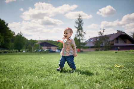 Toddler walking on the green lawn at sunny day.