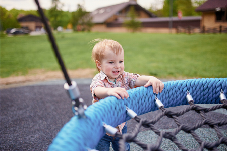Portrait of happy smiling little toddler boy standing near the swings at playground outside on summer day.