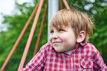 Outdoors portrait of cute preschool boy at the playground on natural green background Фото со стока