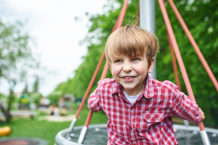 Outdoors portrait of cute preschool boy at the playground on natural green background Stock fotó