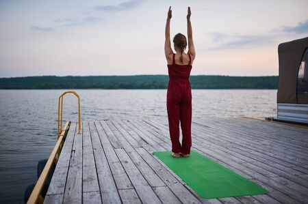 Beautiful young woman practices yoga, mountain pose on the wooden deck near the lake.