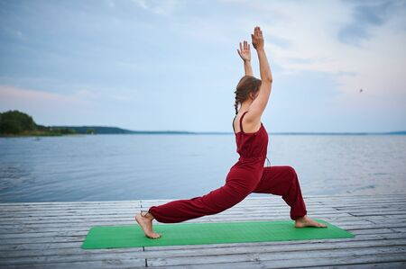 Beautiful young woman practices yoga, warrior pose 1 on the wooden deck near the lake. Stock fotó