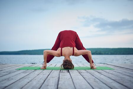 Beautiful young woman practices yoga on the wooden deck near the lake