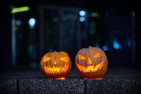 Two glowing Halloween Pumpkins in the city at night. Light the city at night, bokeh