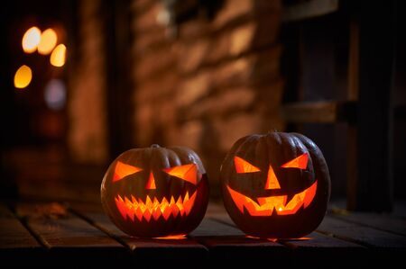 Two glowing Halloween Pumpkins at the entrance to an old wooden house.