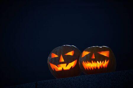Two glowing Halloween Pumpkins on a dark background. Stock fotó