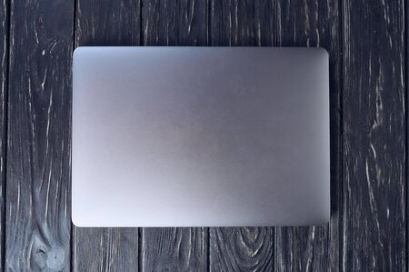 Closed alloy laptop on a wooden background
