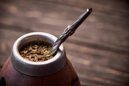 Yerba mate in calabash on dark wooden background.