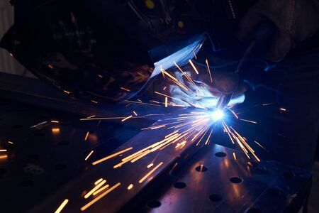 worker with protective mask welding metal closeup. Imagens