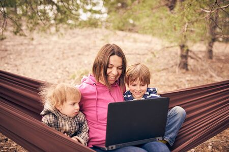 Working away from office concept, woman with two kids working on laptop while lying in hammock in a forest.