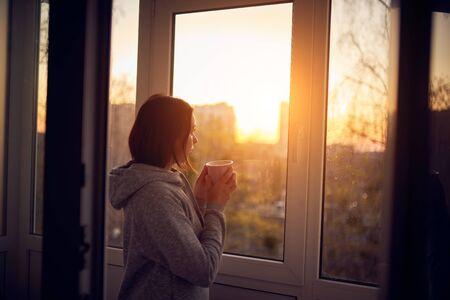 Femme près de la fenêtre au coucher du soleil isolée à la maison pour une épidémie de virus. Concept de séjour à la maison.