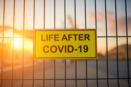 Life After COVID-19 sign on a fence with blured city view on a background at sunset.
