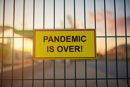 Pandemic is Over sign on a fence with blured city view on a background at sunset.