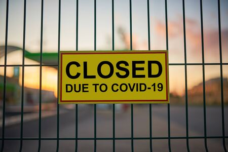 Closed due to COVID-19 sign on a fence with blured city view on a background at sunset. Standard-Bild