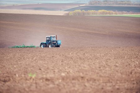 A tractor plowing and sowing in the field.