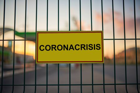 Coronacrisis sign on a fence with blured city view on a background at sunset.