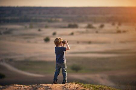 Boy Looking through Binoculars outdoors at sunny day.