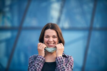 Young happy woman takes off protective medical mask outdoors against modern city background. Pandemic Covid-19 is over concept.