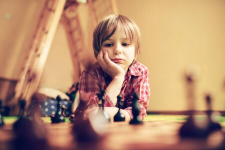 Cute preschool boy are playing chess at home. Funny face, selective focus. Zdjęcie Seryjne