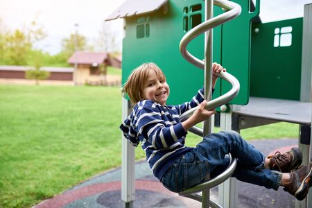 Outdoors portrait of cute preschool boy climbing at the playground.