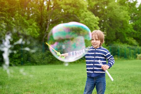 Outdoors portrait of cute preschool boy blowing soap bubbles on a green lawn at the playground