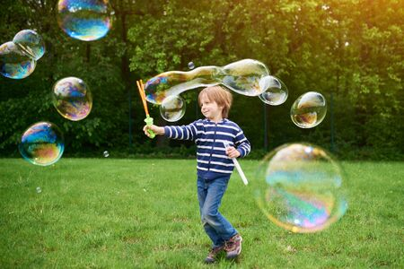 Outdoors portrait of cute preschool boy blowing soap bubbles on a green lawn at the playground Фото со стока - 147261063