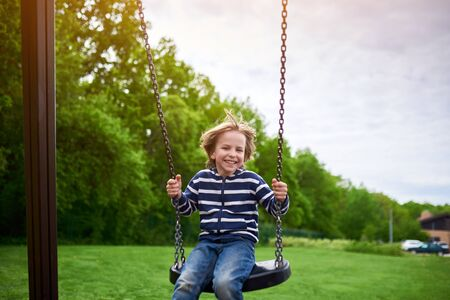 Outdoors portrait of cute preschool laughing boy swinging on a swing at the playground.