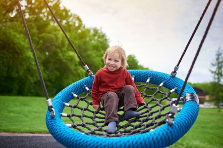 Outdoors portrait of cute 2 year laughing toddler swinging on a swing at the playground.