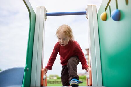 Happy 2 year old toddler playing at the playground. Фото со стока - 147260401