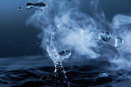 Boiling water splash with steam on dark blue background closeup. Фото со стока