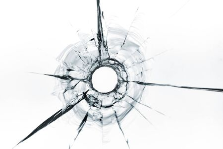 bullet hole in glass close up on white background.