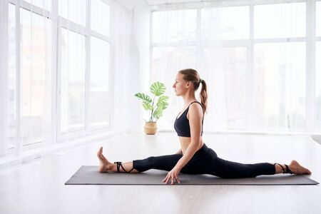 young beautiful woman doing yoga in a modern bright room with large windows at sunny day. Yoga at home concept.